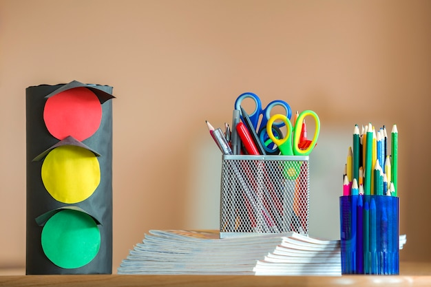 Stos zeszytów, kolorowe kredki do rysowania, sygnalizacja świetlna z zabawkami z papieru.