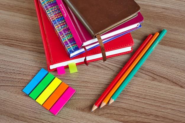Stos zeszytów z ołówkami i kolorowymi zakładkami na drewnianym stole