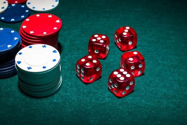 Stos żetonów i czerwone kostki na stole do pokera