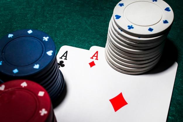 Stos żetonów kasyna w kolorze białym i czerwonym nad brylantami i klubowymi asami