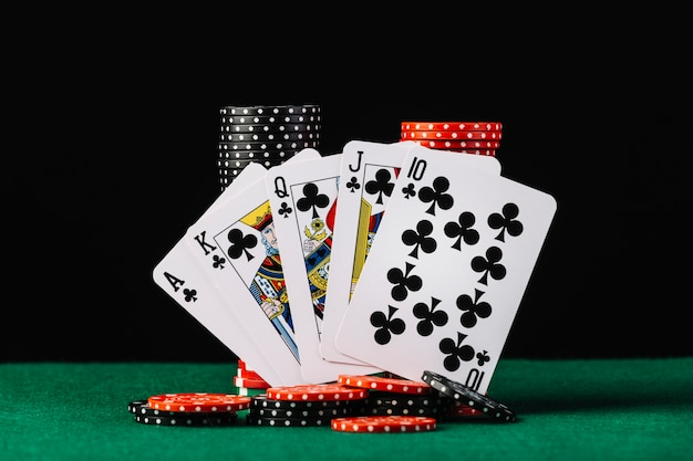 Stos żetonów kasyno i poker królewski flush na zielonym stole pokerowym