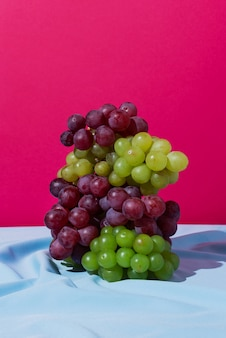 Stos zielonych i czerwonych winogron na niebieskiej draperii