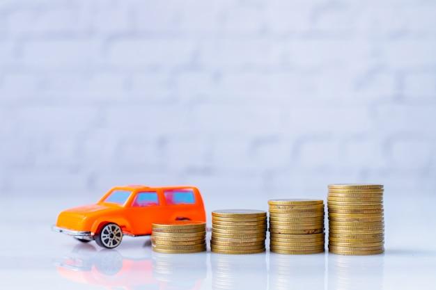 Stos złotych monet i model samochodu