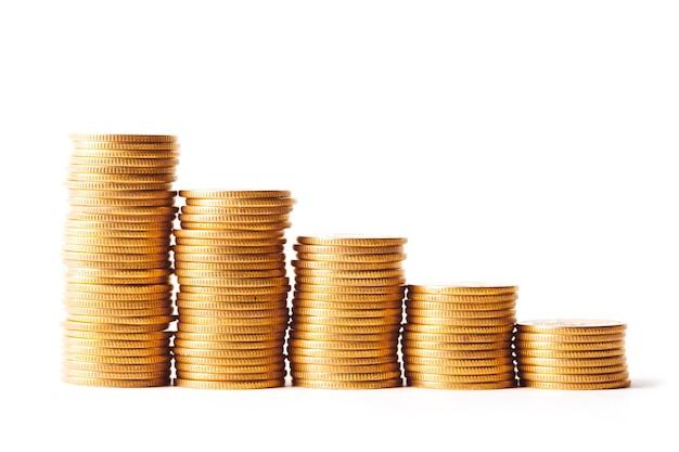 Stos złotych monet na białym tle. strzał studio