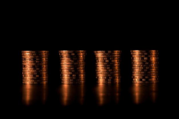 Stos złotych monet w formie wykresu słupkowego na czarnym tle. wykres słupkowy złotych monet.