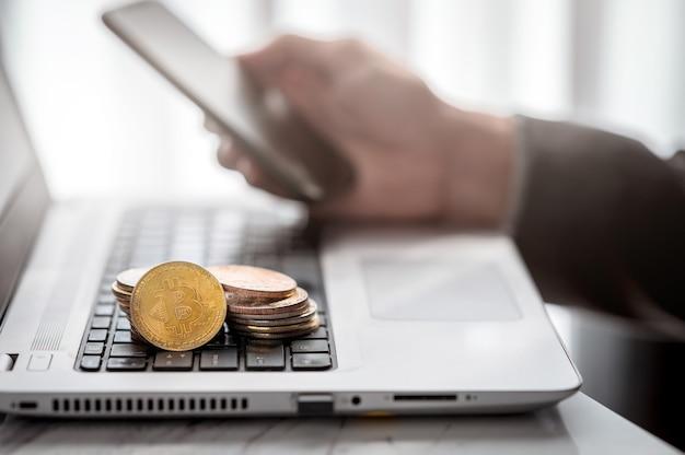 Stos złotych monet z symbolem bitcoin na klawiaturze notebooka ręką biznesmena za pomocą smartfona w tle