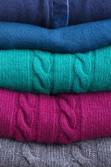 Stos złożonego wełnianego szarego, zielonego, niebieskiego i czerwonego ubrania