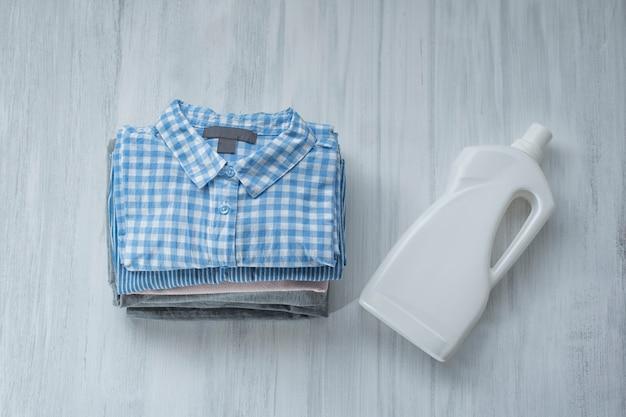 Stos złożonych koszul i butelki z detergentem. widok z góry