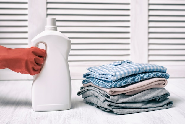 Stos złożonych ubrań i butelkę detergentu w kobiecej dłoni. prace domowe