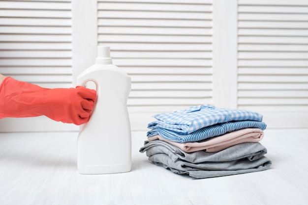 Stos złożonych ubrań i butelkę detergentu w kobiecej dłoni.