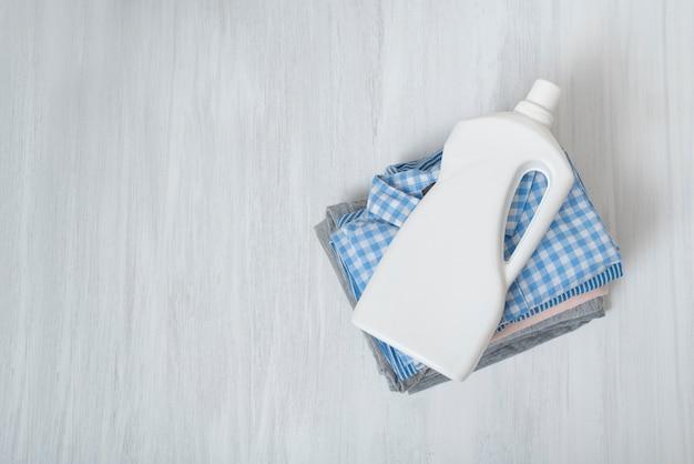 Stos złożonych ubrań i butelki z detergentem. widok z góry