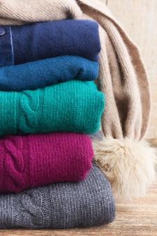 Stos złożonych wełnianych szarej, zielonej, niebieskiej i czerwonej odzieży z bliska