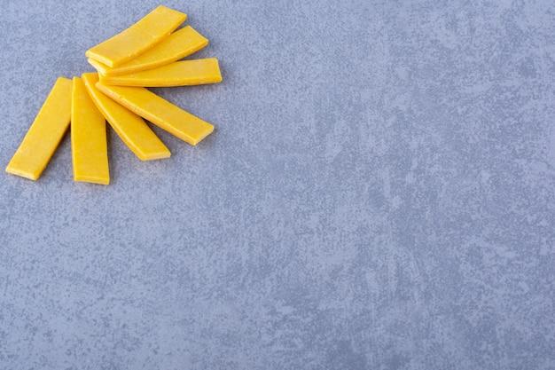 Stos żółtej gumy do żucia wbija się w marmurową powierzchnię
