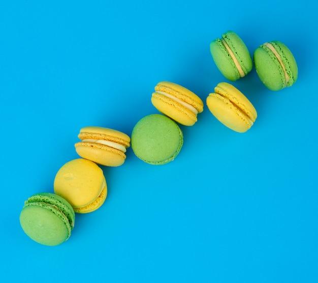 Stos żółtej i zielonej okrągłej mąki migdałowej ciasta makaroniki ze śmietaną