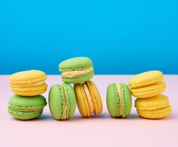 Stos żółty i zielony okrągły mąki migdałowej ciasta macarons ze śmietaną na niebieskiej przestrzeni