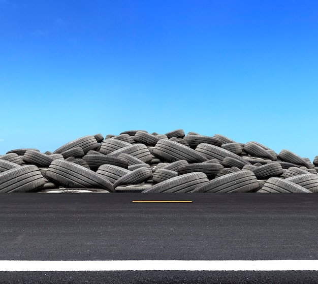 Stos zużytych gumowych opon na drodze z nadmiernym światłem na tle błękitnego nieba