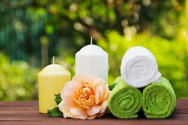 Stos zwiniętych ręczników, świec i pachnących róż.