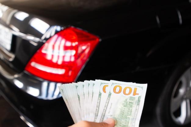 Stosu sto nowego dolara amerykańskiego na rękę przed luksusowy samochód na deseń