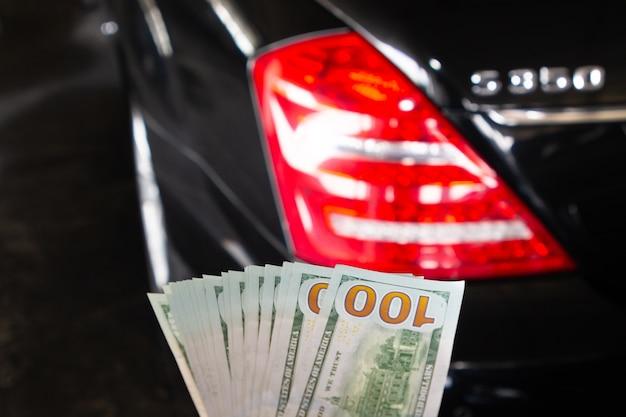 Stosu sto nowego dolara amerykańskiego na rękę przed luksusowy samochód na tle