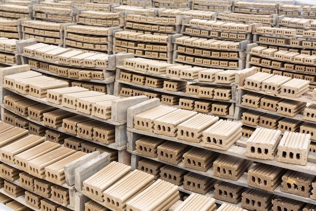 Stosy cegieł umieszczone na podłodze fabryki.