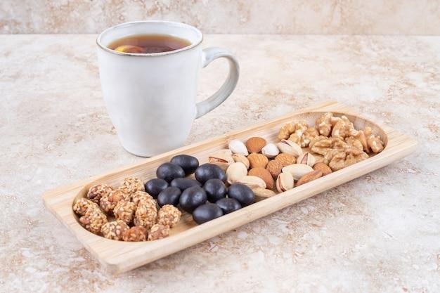 Stosy cukierków i różnych orzechów na małej tacy obok kubka do herbaty