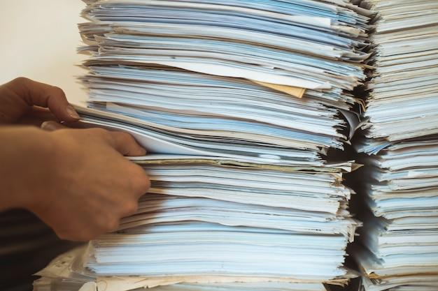 Stosy dokumentów papierowych, raportów finansowych.