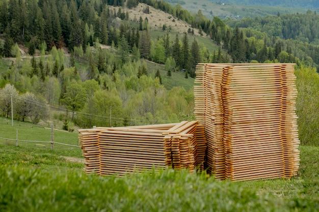 Stosy drewniane deski na zielonej trawie z górami na tle, zaszaluje dla budowy. stos drewna tarcicy z surowego materiału budowlanego