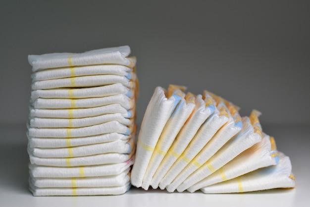 Stosy jednorazowych pieluch zbliżenie na szarym tle stosy pieluch na szarym tle