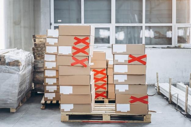 Stosy kartonów z produktami w fabrycznym warsztacie opakowaniowym. niektóre z nich są oznaczone biurokracją