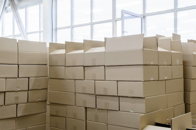 Stosy kartonów z produktami w warsztacie pakowania