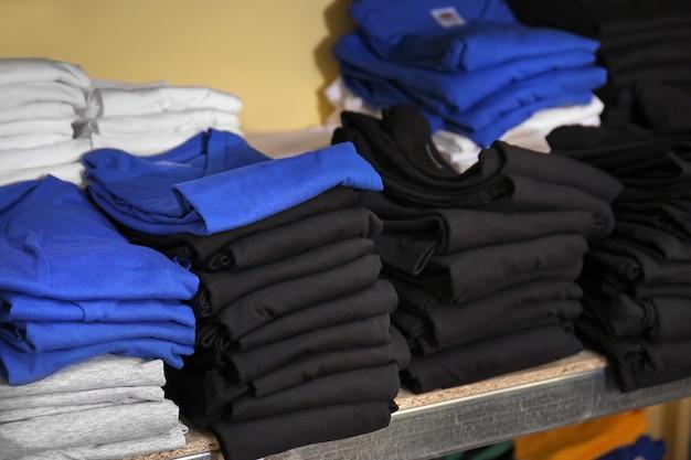 Stosy koszulek przygotowane do nadruku na półce