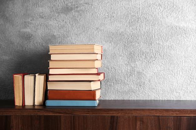 Stosy książek na drewnianej komodzie na szarym tle ściany
