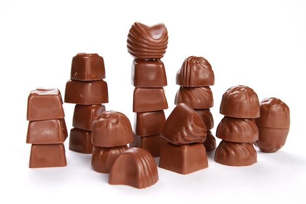 Stosy małych ozdobnych czekoladek na białym tle