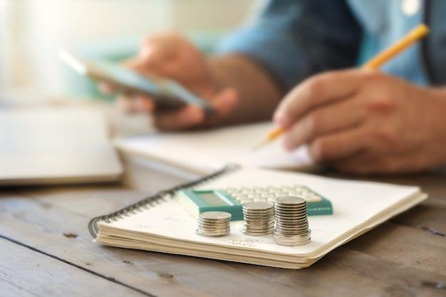 Stosy monet na drewnianym stole z kalkulatorem. opodatkowanie, księgowość domowa lub analiza kredytowa dla koncepcji spłaty kredytu hipotecznego