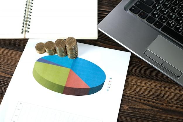 Stosy monet z laptopa notebooka i wykres finansowy na białym papierze