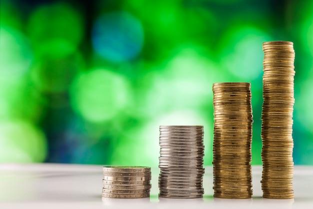 Stosy monet z zielonym tłem.