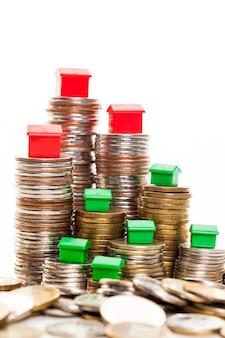 Stosy monet, zielony i czerwony dom. pojęcie kredytu hipotecznego przez dom pieniędzy z monet