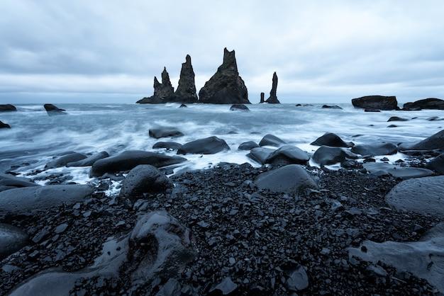 Stosy morskie reynisdrangar w pobliżu plaży reynisfjara przy nadmorskiej wiosce vik, islandia