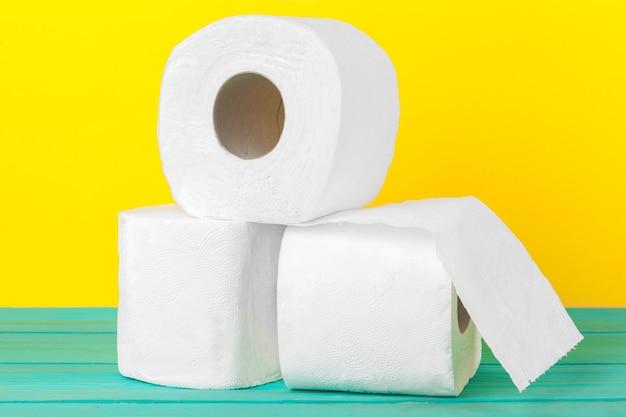 Stosy papieru toaletowego na jasnym żółtym tle