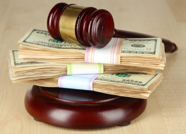 Stosy pieniędzy i młotek sędziowski na drewnianym stole