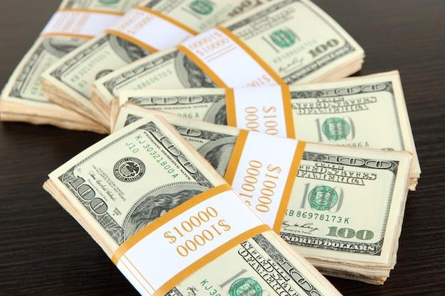 Stosy pieniędzy na drewnianym stole