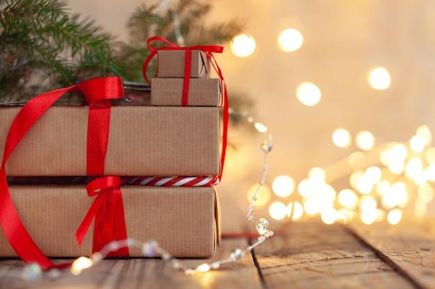 Stosy prezentów bożonarodzeniowych ułożone pod choinką z niewyraźnymi światłami.