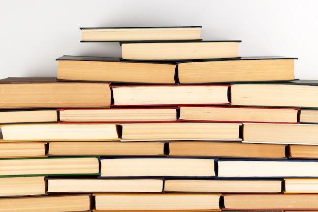 Stosy różnych książek w twardej oprawie na białym tle