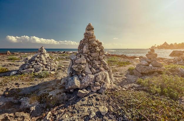 Stosy skał zen w środku skalistego wybrzeża puerto aventuras na riwierze majów w meksyku o zachodzie słońca.