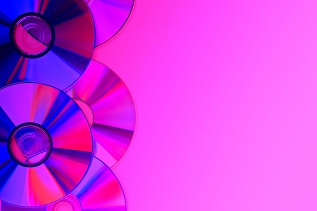 Stosy starych i brudnych płyt cd, dvd na fioletowym neonie