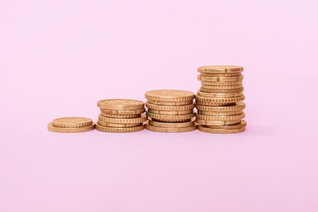 Stosy z monetami euro na różowym tle. złote monety rosną. zbliżenie.