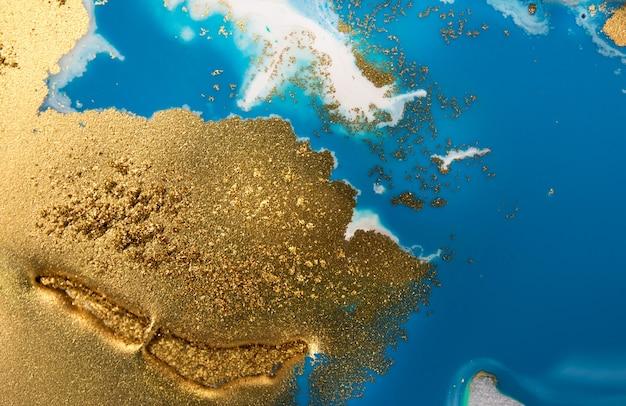 Stosy złotych cekinów na niebieskich plamach farby. streszczenie wylewanie farby