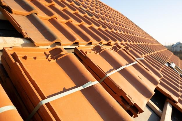Stosy żółtej dachówki ceramicznej do pokrycia dachu budynku mieszkalnego w budowie.