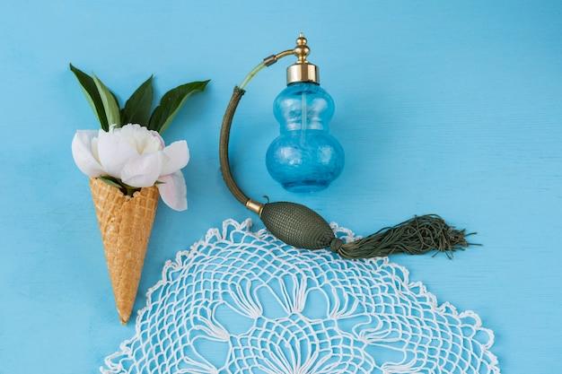 Stożek do lodów, aw nim biała piwonia, obrus z koronki i butelka starych perfum