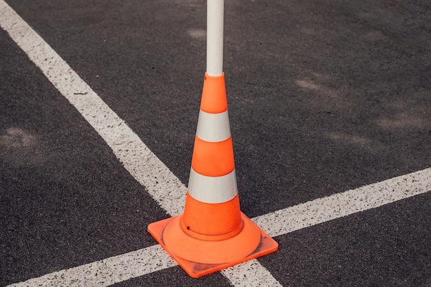 Stożek drogowy na przecięciu białych linii oznaczeń drogowych.